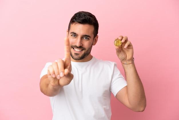 Молодой человек, держащий биткойн на розовом фоне, показывает и поднимает палец