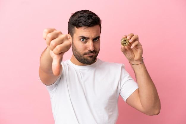 Молодой человек держит биткойн на розовом фоне, показывая большой палец вниз с отрицательным выражением лица