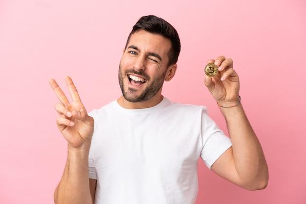 Молодой человек держит биткойн на розовом фоне улыбается и показывает знак победы