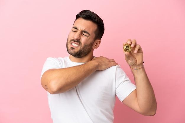 努力したために肩の痛みに苦しんでいるピンクの背景に分離されたビットコインを保持している若い男