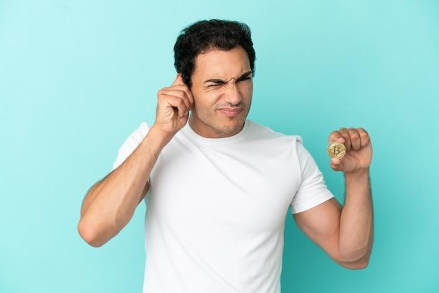 Молодой человек, держащий биткойн на изолированном синем фоне, разочарован и закрывает уши