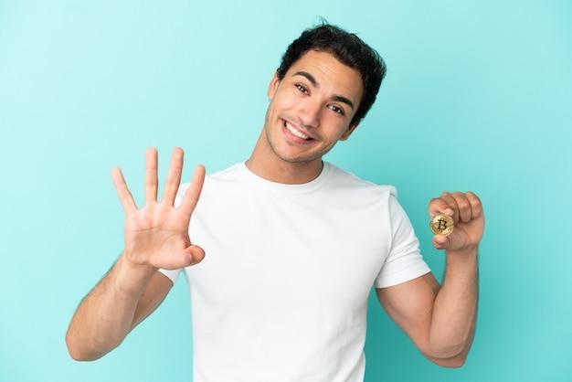 Молодой человек, держащий биткойн на изолированном синем фоне, счастлив и считает четыре пальцами
