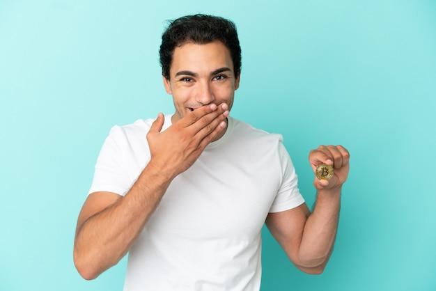 Молодой человек, держащий биткойн на изолированном синем фоне, счастливый и улыбающийся, прикрывая рот рукой