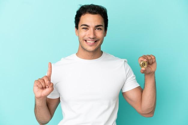 Молодой человек, держащий биткойн на изолированном синем фоне, показывает и поднимает палец в знак лучших