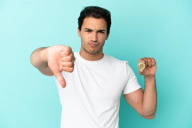 부정적인 표정으로 엄지손가락을 아래로 보여주는 고립된 파란색 배경 위에 bitcoin을 들고 있는 젊은 남자