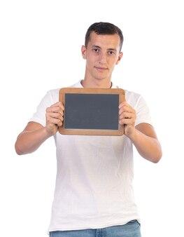 Молодой человек держит доску, чтобы писать на ней на белой стене
