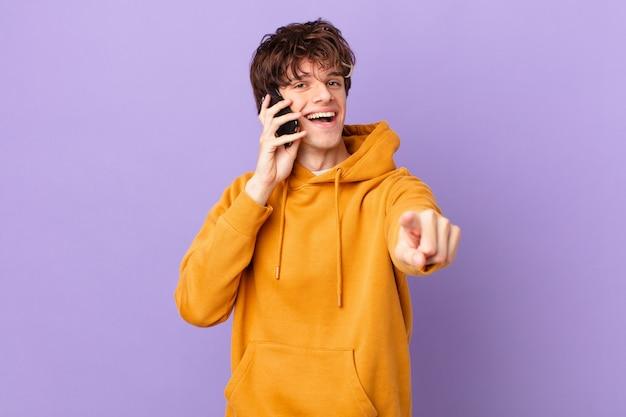 あなたを選ぶカメラを指しているセルを保持している若い男
