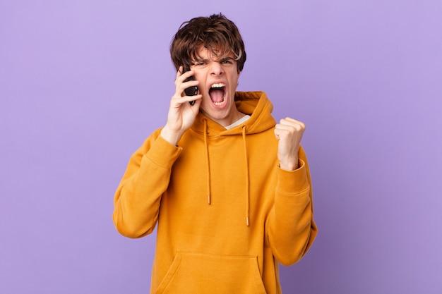 怒りの表情で積極的に叫んでいるセルを保持している若い男