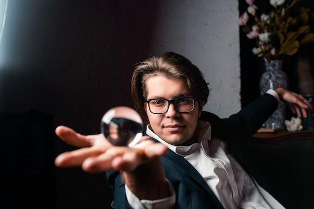 透明な透明なクリスタルガラスのボールを手に持って若い男