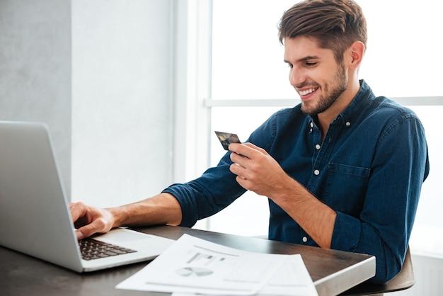 クレジットカードを持って入力している若い男。ラップトップを使用したインターネットでのオンラインショッピング。ラップトップを見て
