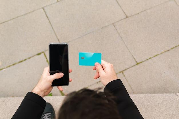 クレジットカードを持っていて、オンラインでの購入と支払いにスマートフォンを使用している若い男性が、インターネット、オンライン支払い、テクノロジー、ビジネスファイナンスで購入しています。