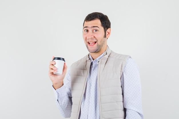 一杯のコーヒーを持って、ベージュのジャケットとキャップで笑って、幸せそうに見える若い男。正面図。