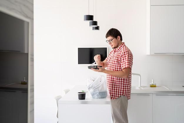 현대 부엌에서 음식 배달과 함께 일회용 비닐 봉지를 들고 있는 청년