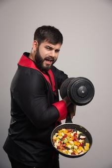 Молодой человек держит гантель и сковороду с овощами.