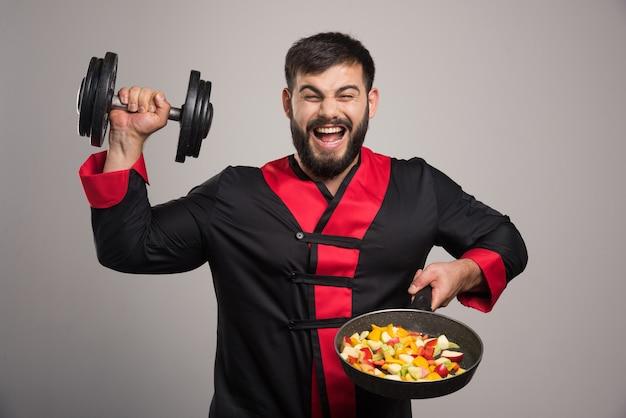 Молодой человек держит гантель и сковороду с овощами. Бесплатные Фотографии