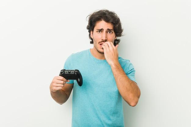 Молодой человек держит игровой контроллер, кусает ногти, нервничает и очень беспокоится.