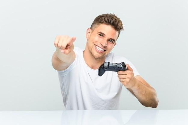 Молодой человек, держащий игровой контроллер веселые улыбки, указывая на фронт.