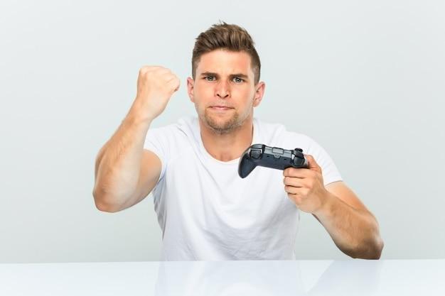 Молодой человек держа регулятор игры показывая кулак к камере, агрессивное выражение лица.