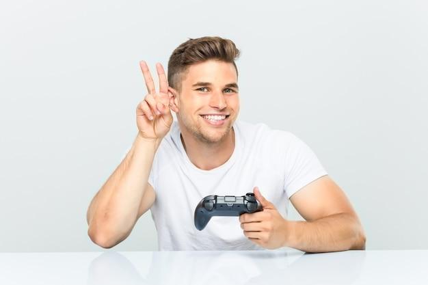 Молодой человек, держащий игровой контроллер, показывает знак победы и широко улыбается.