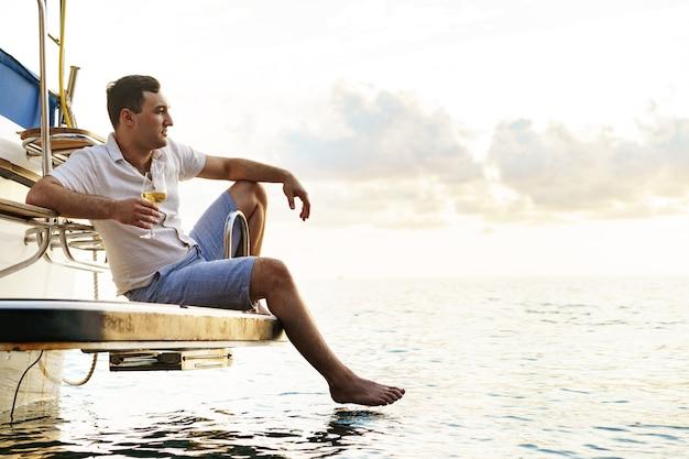 Молодой человек держит бокал вина на открытой палубе круизного судна