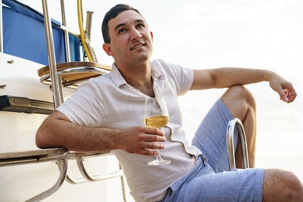 유람선의 오픈 데크에서 와인 한 잔을 들고 있는 청년