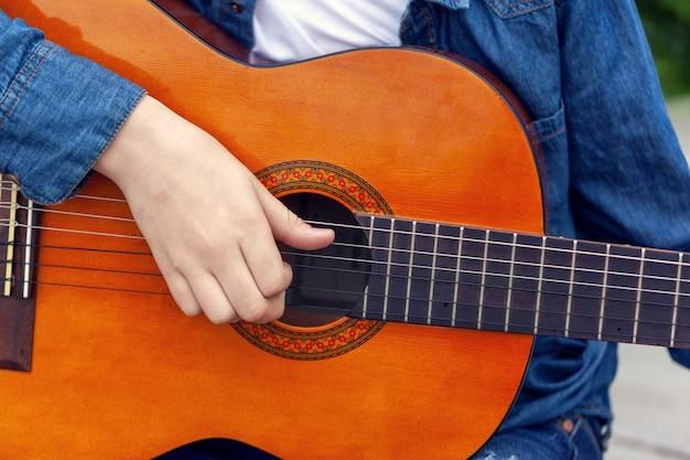 Молодой человек держа гитару и играя музыку.