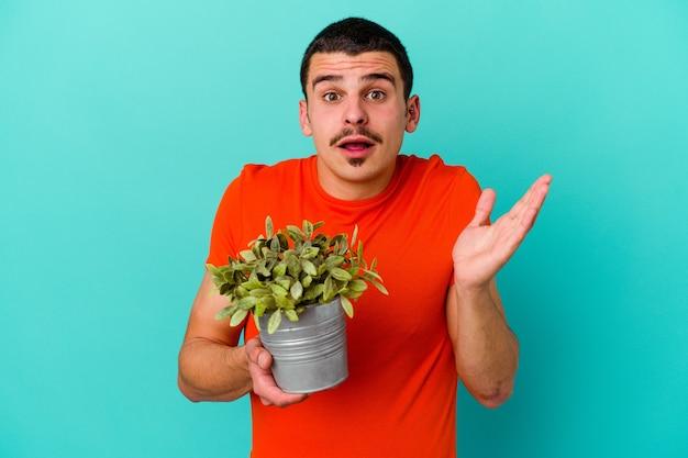 青い壁に孤立した葉を保持している若い男は驚いてショックを受けた