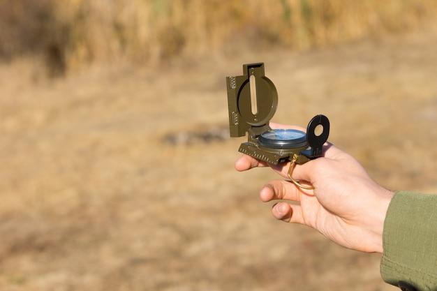 彼はナビゲーションと彼の地理的位置を見つけるためにそれを使用して田舎の屋外に立っているときに磁気コンパスを保持している若い男