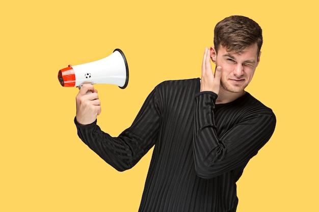 黄色のスタジオの背景にメガホンを保持している若い男