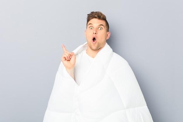 Молодой человек, держащий пуховое одеяло, имеющий отличную идею, концепцию творчества.
