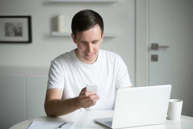 若い男は、電話を持って、机の上に座って、近くのラップトップ