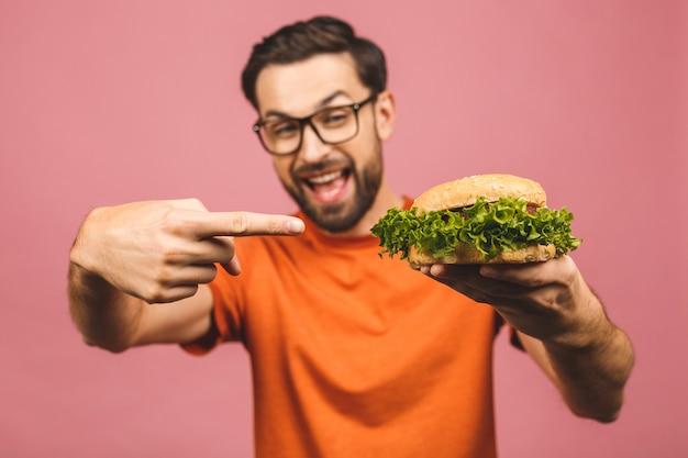 Молодой человек держит кусок гамбургера. бургер не полезная еда. очень голодный парень.