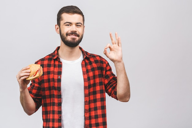 Молодой человек держит кусок гамбургера. концепция диеты изолированная против белой предпосылки. хорошо знаком.