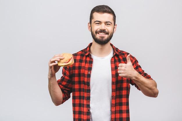 ハンバーガーの部分を保持している若い男。白い背景に対して隔離される食事概念。いいぞ。