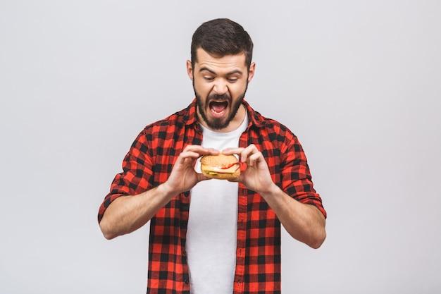 Молодой человек держит кусок гамбургера. концепция диеты изолированная против белой предпосылки.