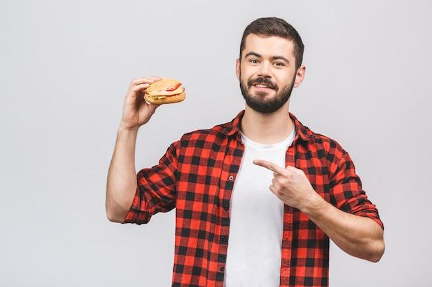 ハンバーガーの部分を保持している若い男。白い背景に対して隔離される食事概念。