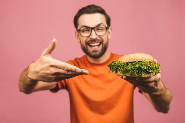 Молодой человек держит кусок гамбургера. студент ест фаст-фуд. очень голодный парень.