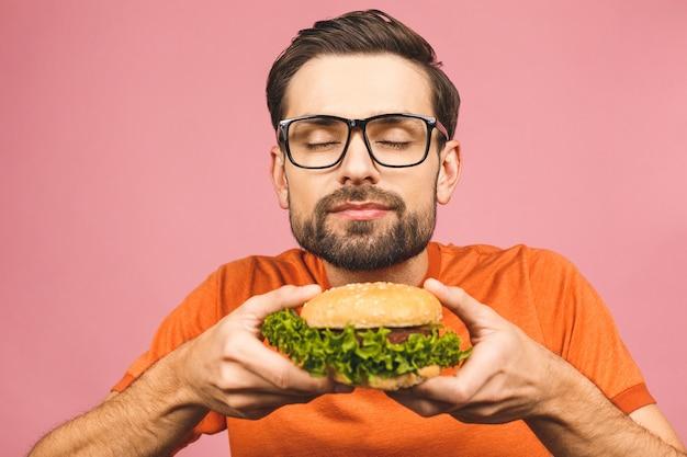 ハンバーガーの部分を保持している若い男