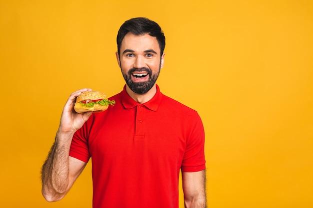 샌드위치 한 조각을 들고 젊은 남자. 학생은 패스트 푸드를 먹습니다. 버거는 도움이되는 음식이 아닙니다.