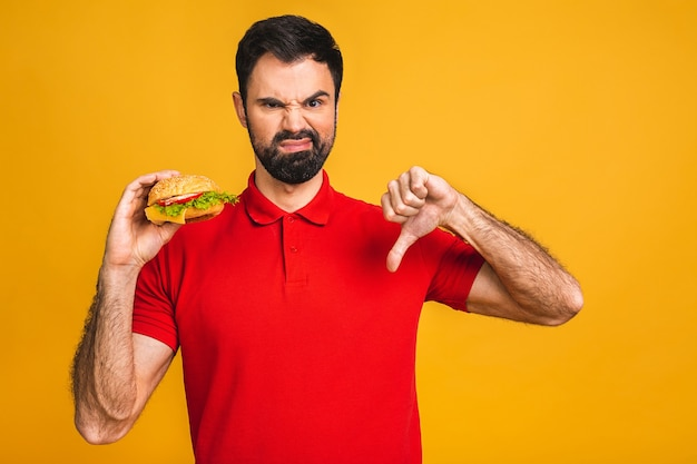 Молодой человек держит кусок бутерброда. студент ест фаст-фуд. бургер - бесполезная еда.