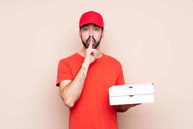 입에 손가락을 넣어 침묵 제스처의 표시를 보여주는 피자를 들고 젊은 남자