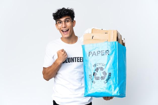 Молодой человек держит мешок для переработки, полный бумаги, празднует победу