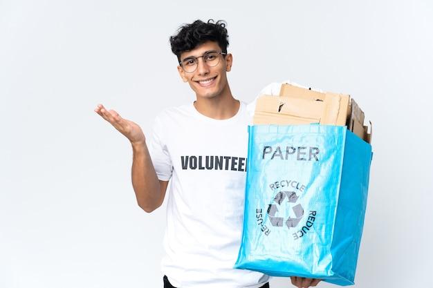 紙でいっぱいのリサイクルバッグを持って、手を横に伸ばして招待する青年