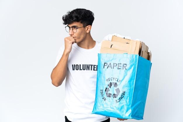 Молодой человек, держащий мешок для переработки, полный бумаги, сомневаясь