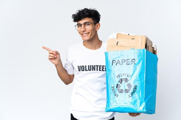 Молодой человек держит мешок для переработки, полный бумаги, указывая пальцем в сторону