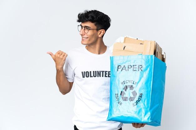 제품을 제시하기 위해 측면을 가리키는 종이로 가득 찬 재활용 가방을 들고 젊은 남자