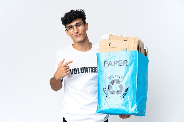 製品を提示するために側面を指している紙でいっぱいのリサイクルバッグを持っている若い男