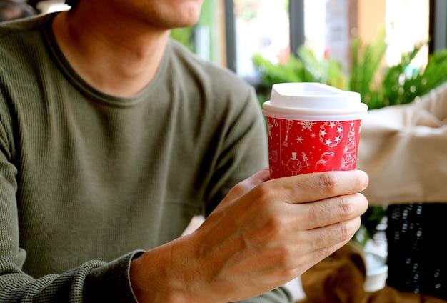 빨간색과 흰색 테이크 아웃 커피 컵을 손에 들고 젊은 남자