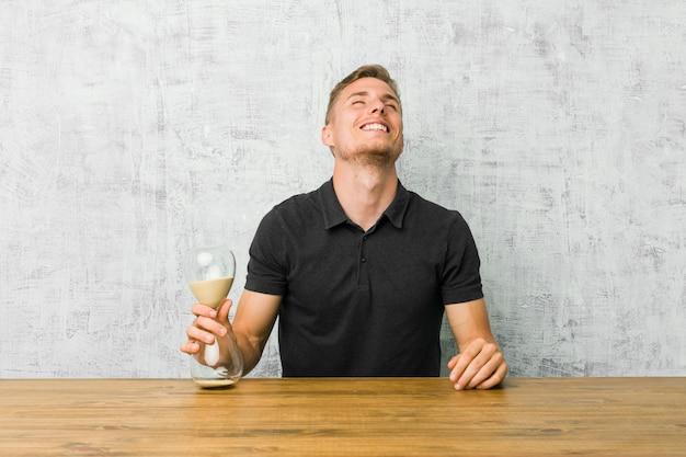 테이블에 모래 타이머를 들고 젊은 남자 편안하고 행복한 웃음, 목 뻗어 보여주는 이빨.