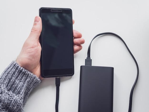 Молодой человек держит смартфон, подключенный к power bank